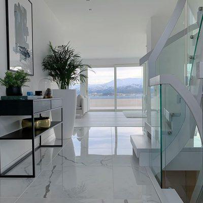 Valkoiset marmorilattiat korostavat upealla tavalla sisustuksen minimalistista ja mustavalkoista tyyliä.